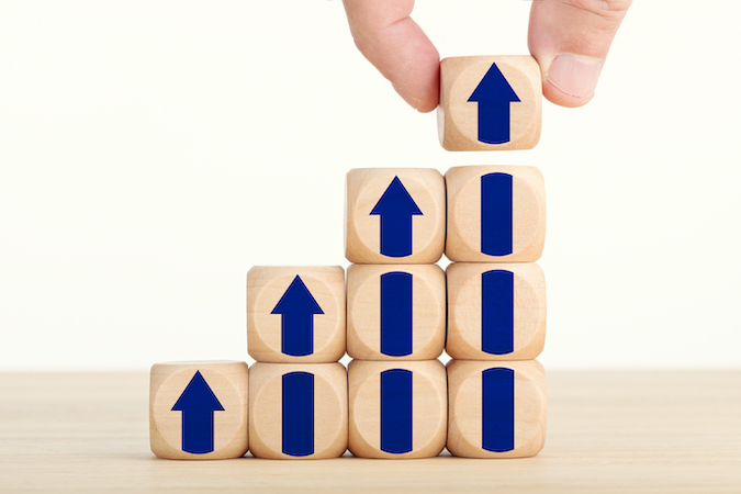 wooden blocks with arrows pointing up on them and a hand stacking them higher