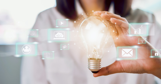 woman with a lit lightbulb in her hand with overlaid marketing icons
